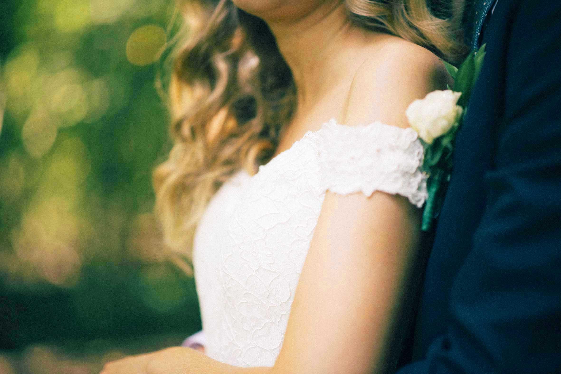 Detalj bilde av hvit kjole til brud, grønn skog bak