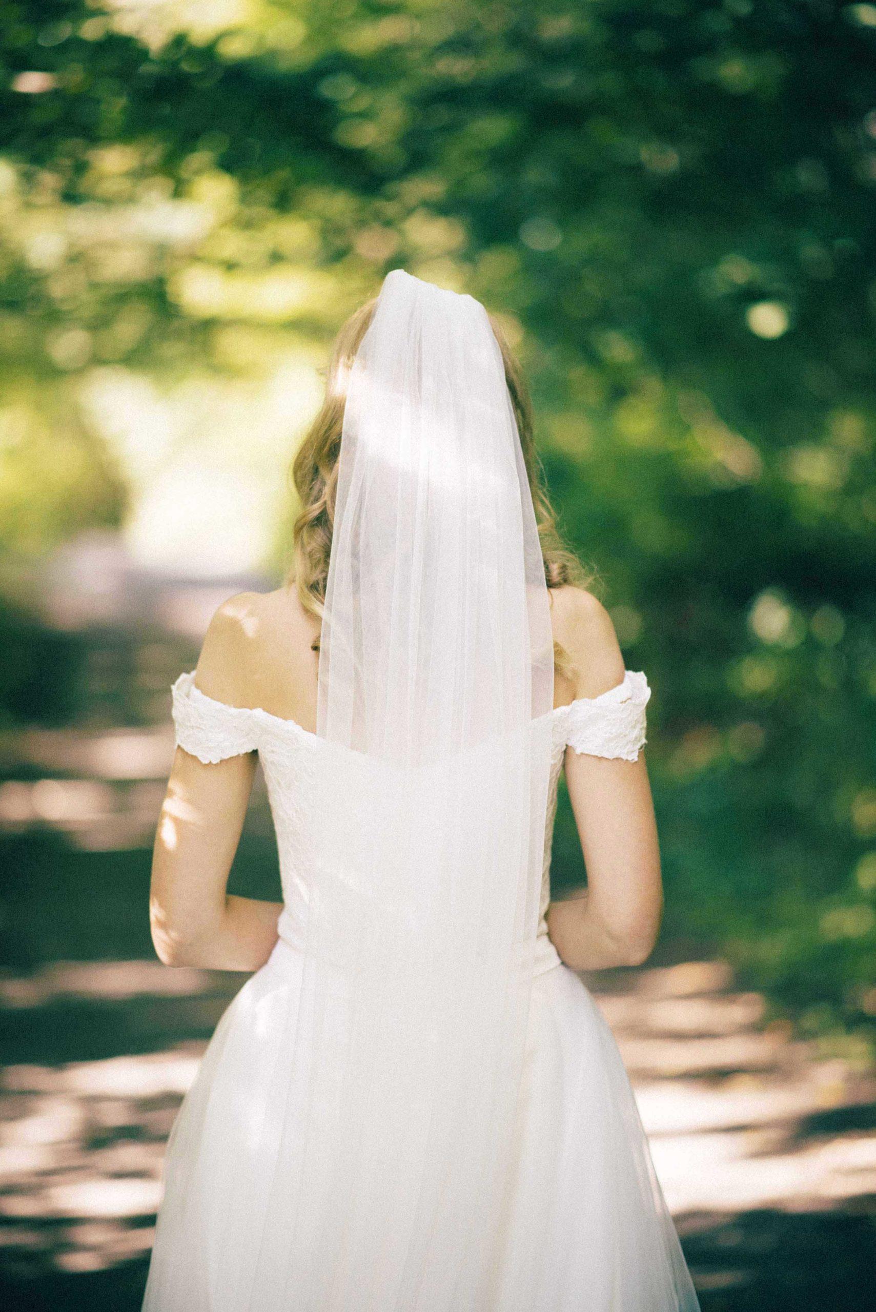 Høstbryllup fra Oslo. Bilde av ryggen til bruden. Hun står i skogen.