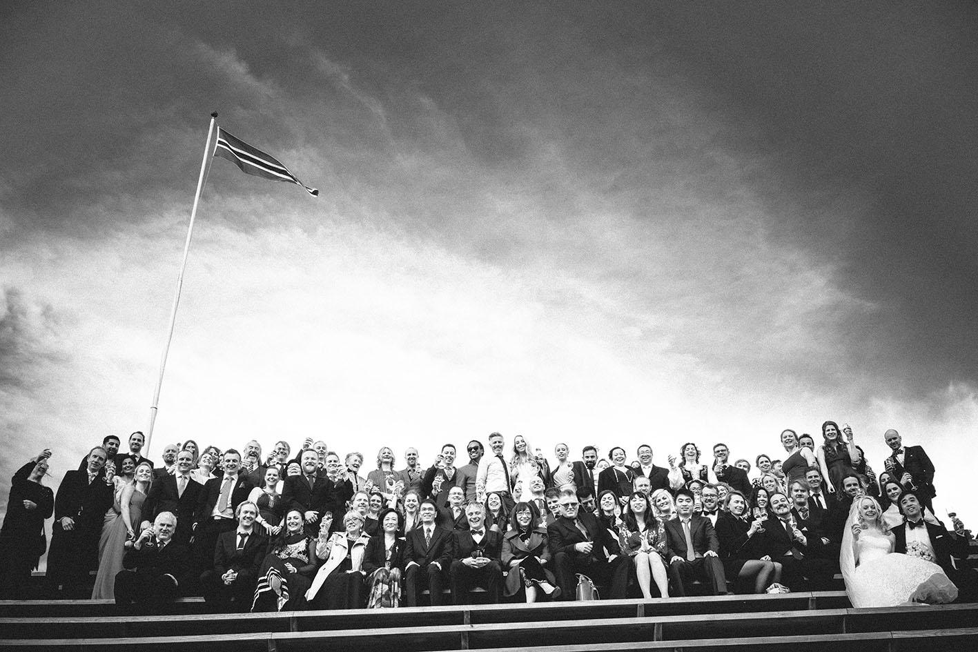 Samle bilde av alle gjester med det norske flagget i bakgrunnen, tatt av bryllupsfotograf Oslo