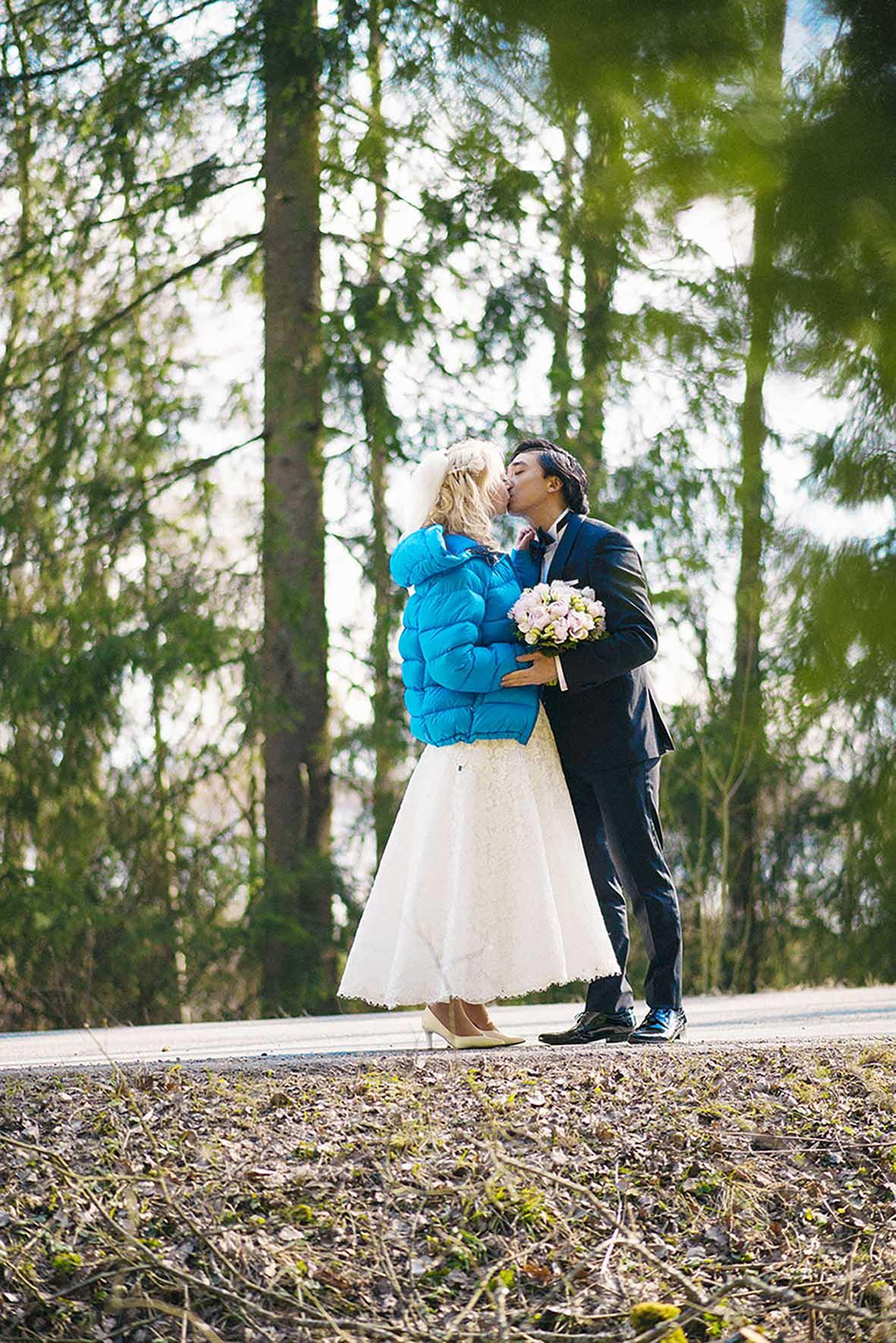 Blå jakke, brud og brudgom kysser I skogen