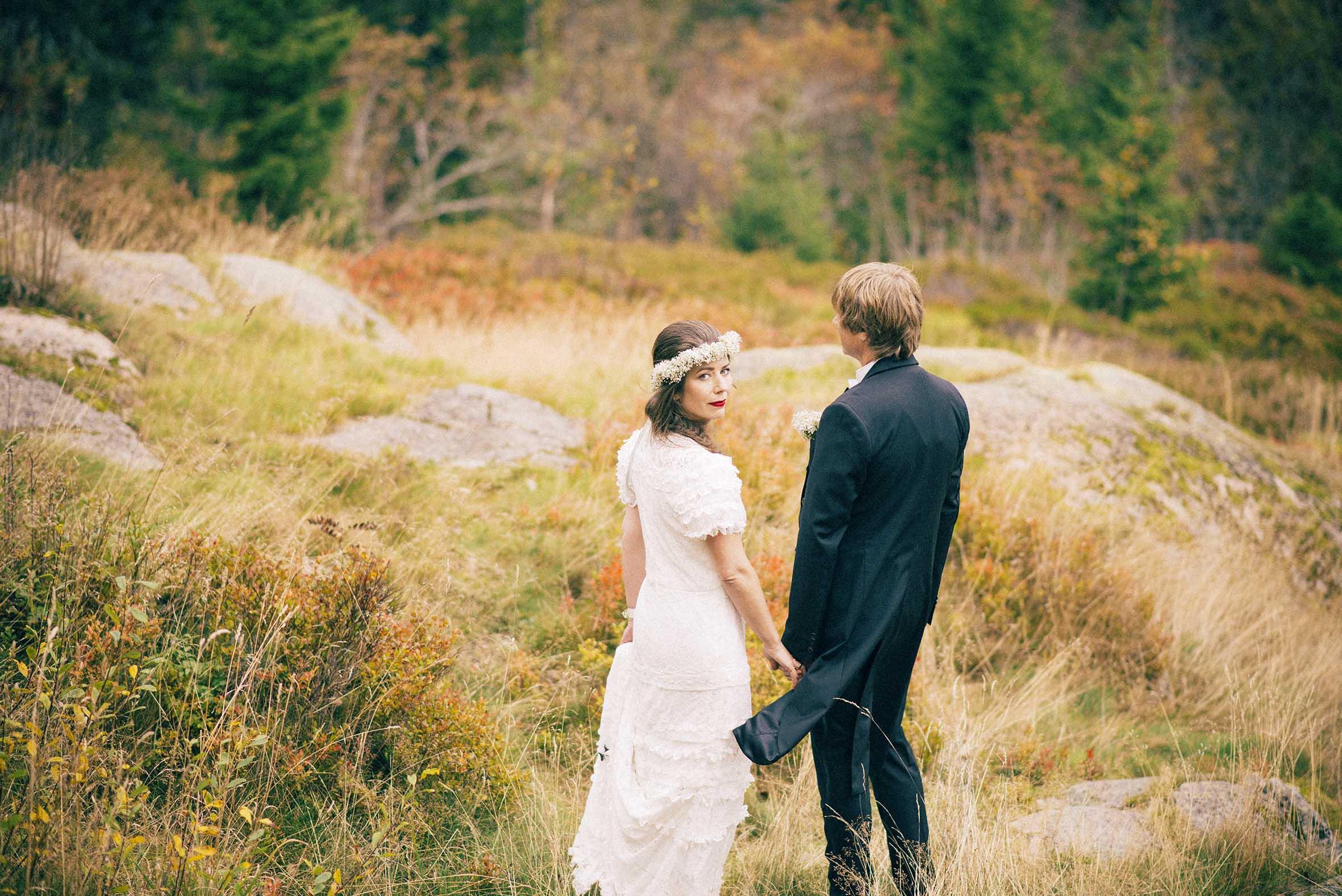 Nostalgisk bryllupsbilde, brudgommen har en frakk som blåser i vinden, bruden ser inn i kamera, romantisk bilde, bryllups fotografering fra Soria Moria