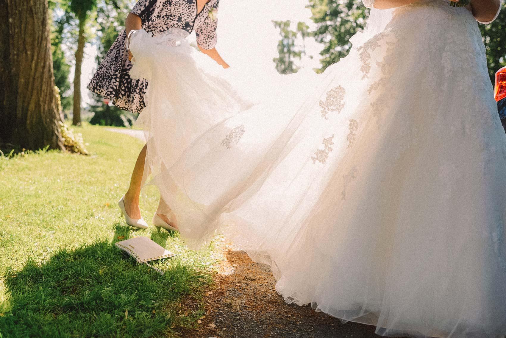 Brudekjole i solen, brud gjør seg klar til å gå inn i kirke