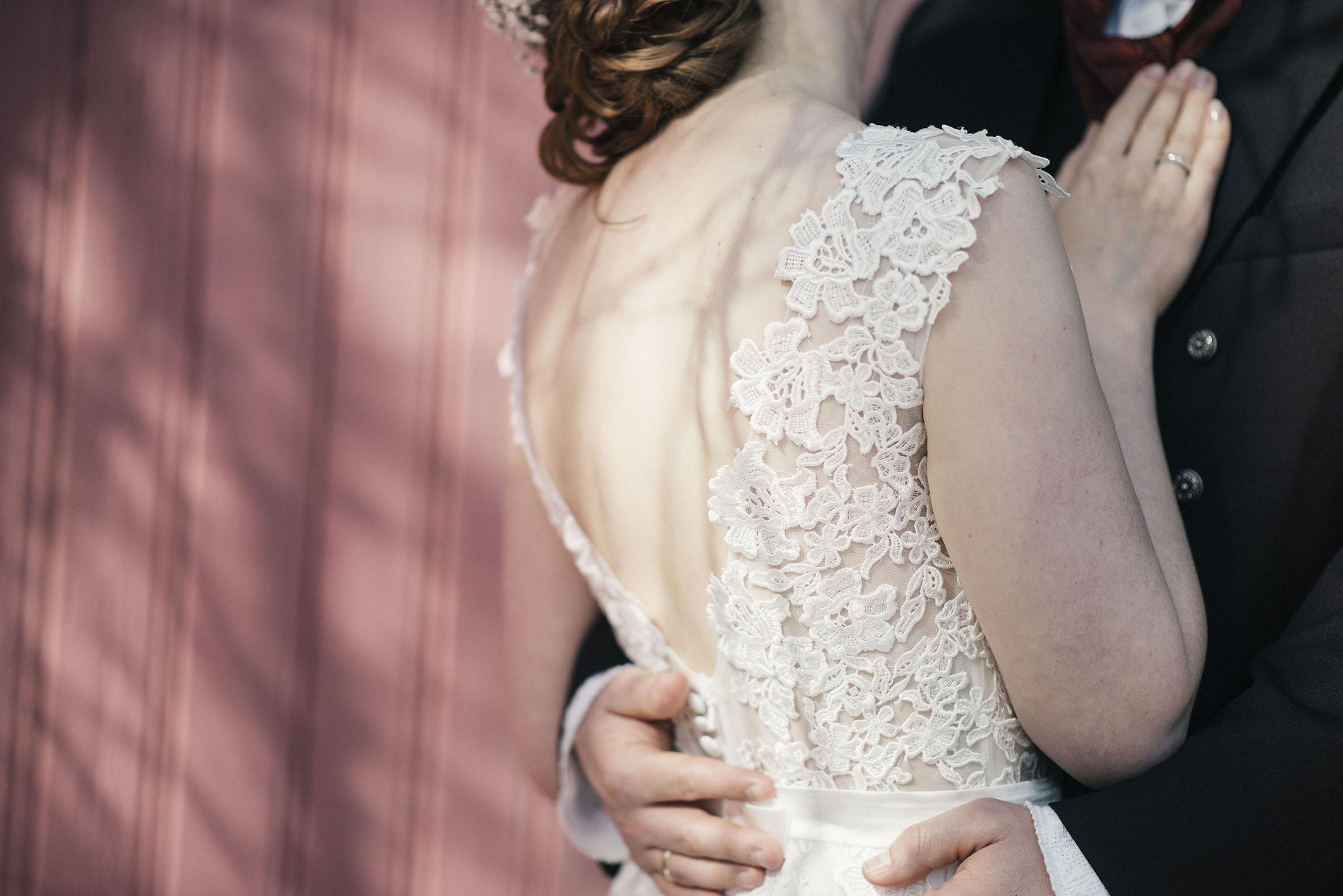 detalj bilde av rygg til brud, rosa vegg som bakgrunn