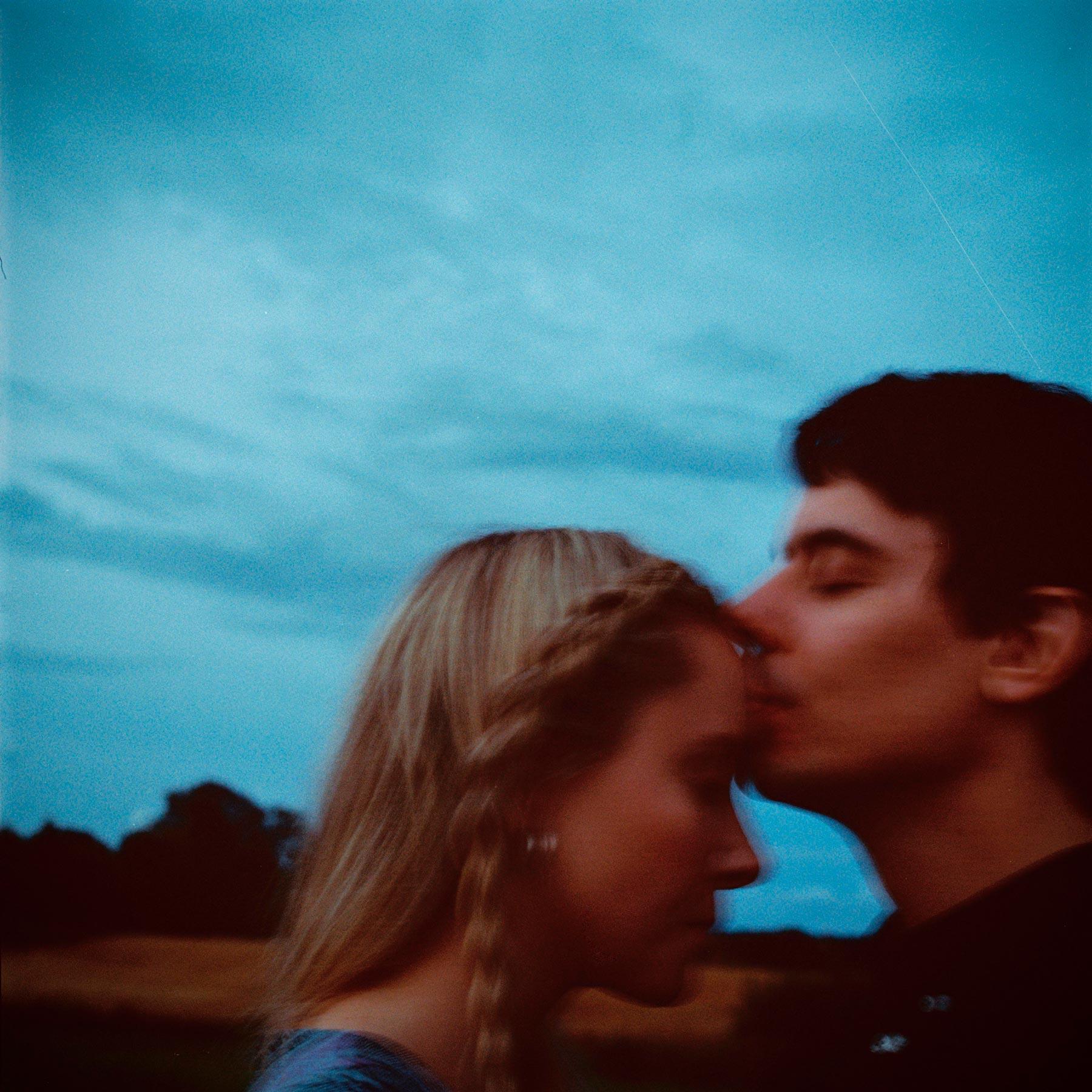 Mann kysser kvinne på pannen, tatt av bryllupsfotograf Oslo