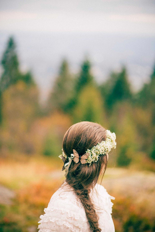 Høstbryllup fra Oslo.Brud står i skogen med blomster i håret