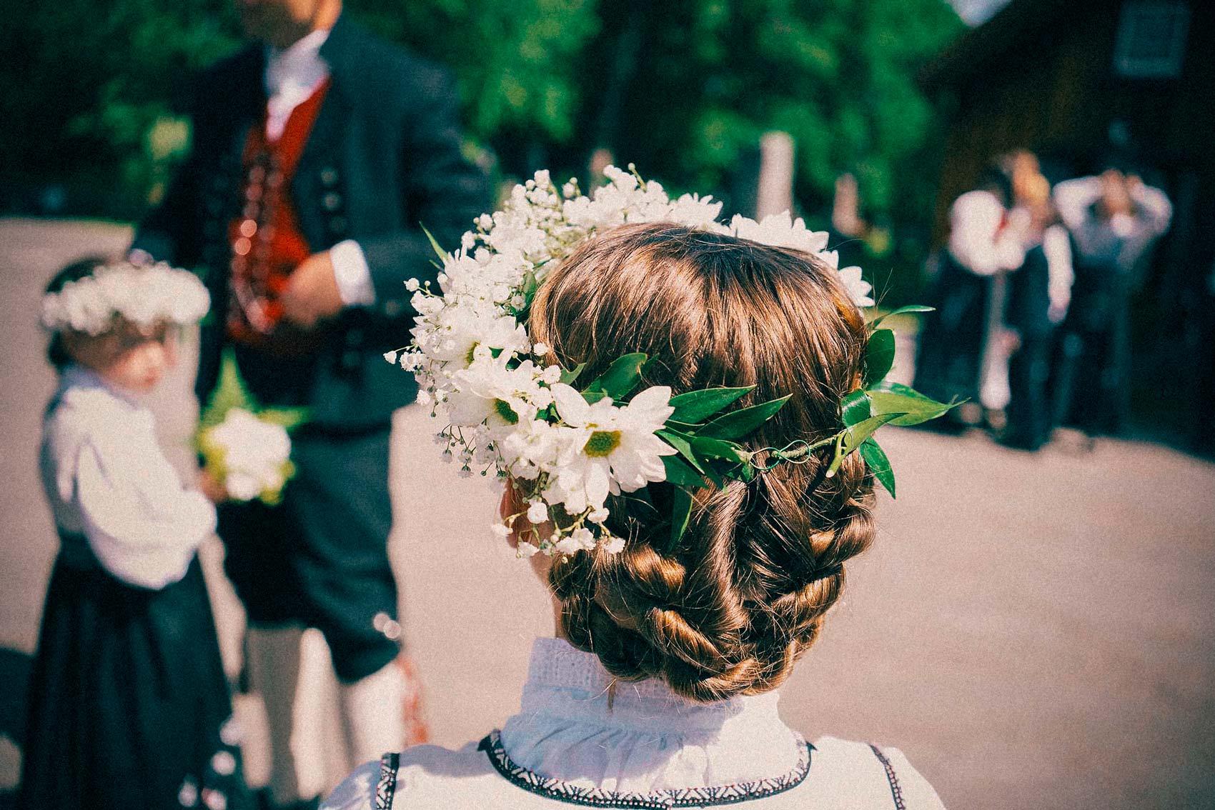pike med bunad er gjest i bryllup, hun har blomster i håret