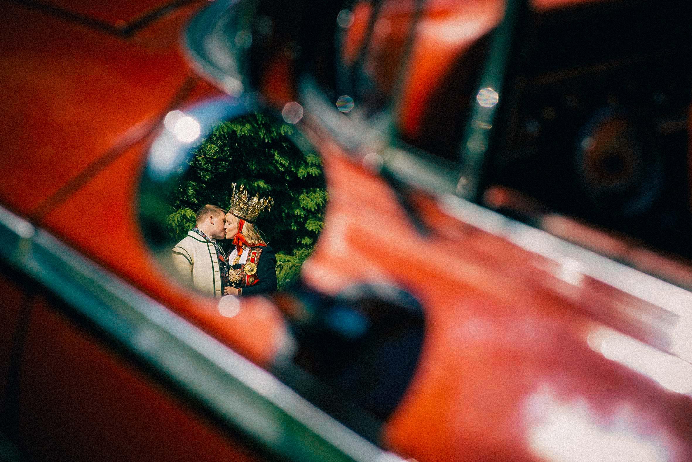 brud og brudgom kysser i speilet til en rød bil
