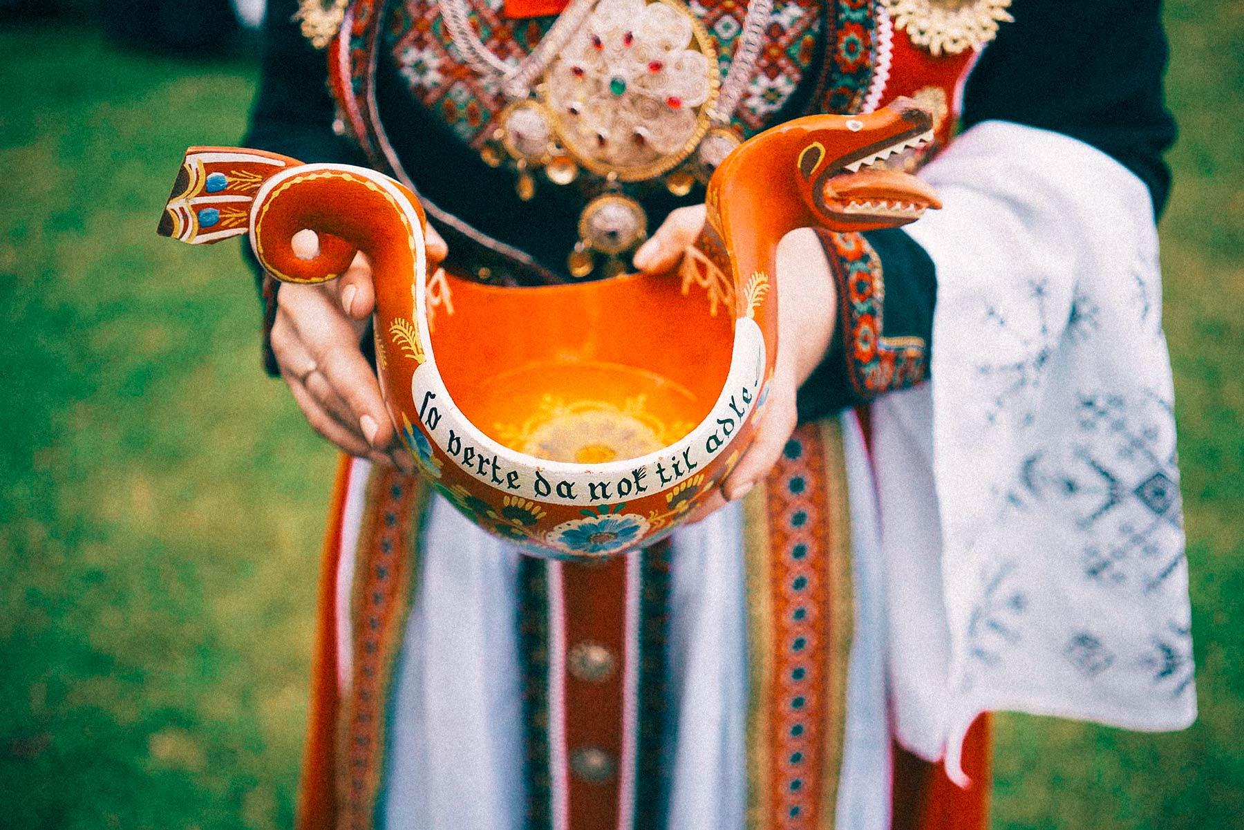 brud i bunad holder en gammel kopp