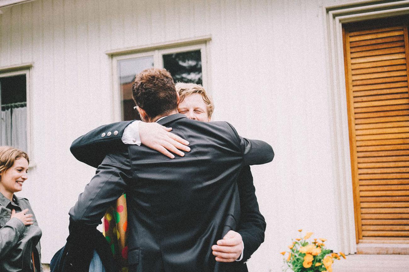 Bryllupsfotografering fra Hamar. Brudgom klemmer en gjest