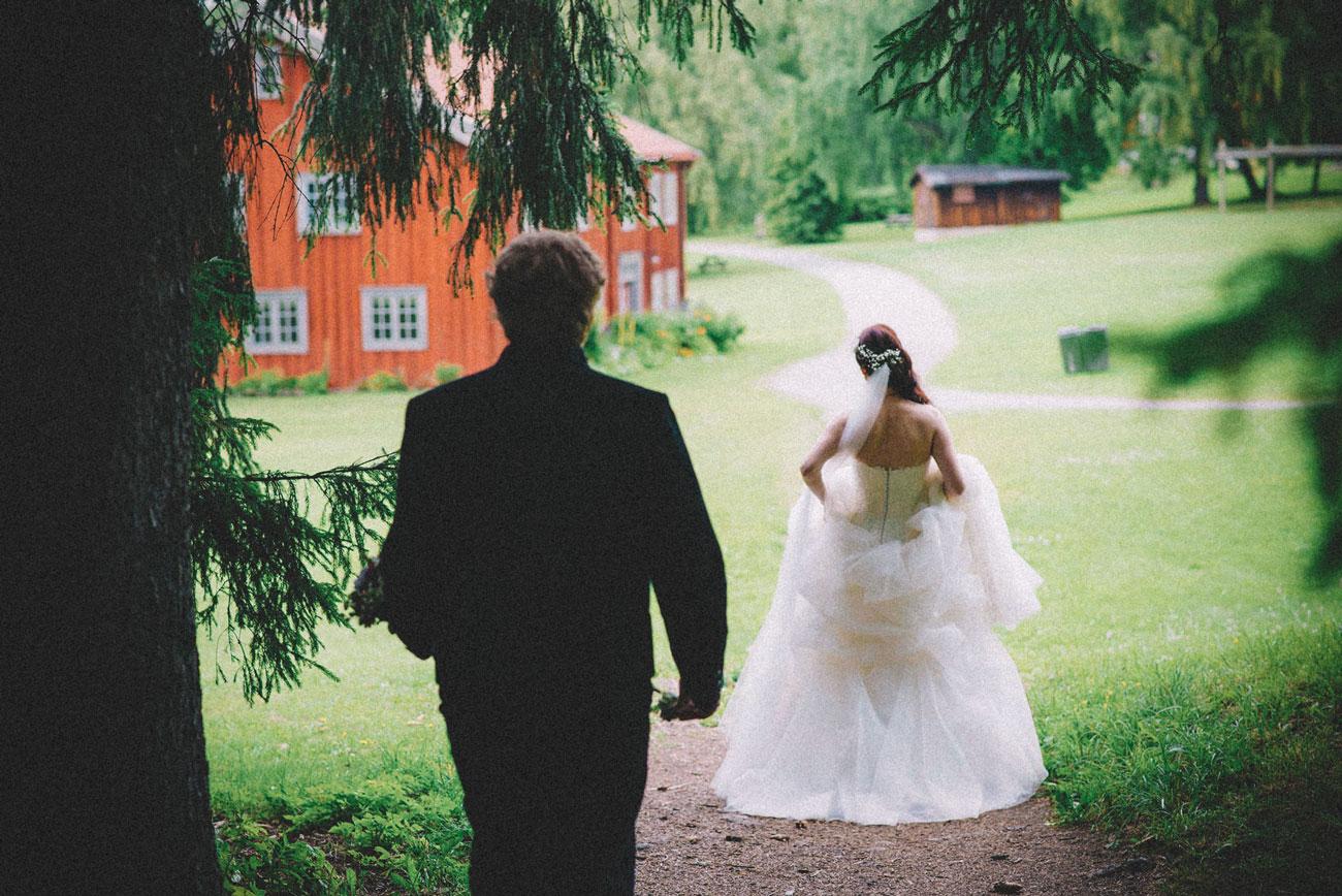 Bryllupsfotografering fra Mjøsa. Nygift par vandrer over gresset