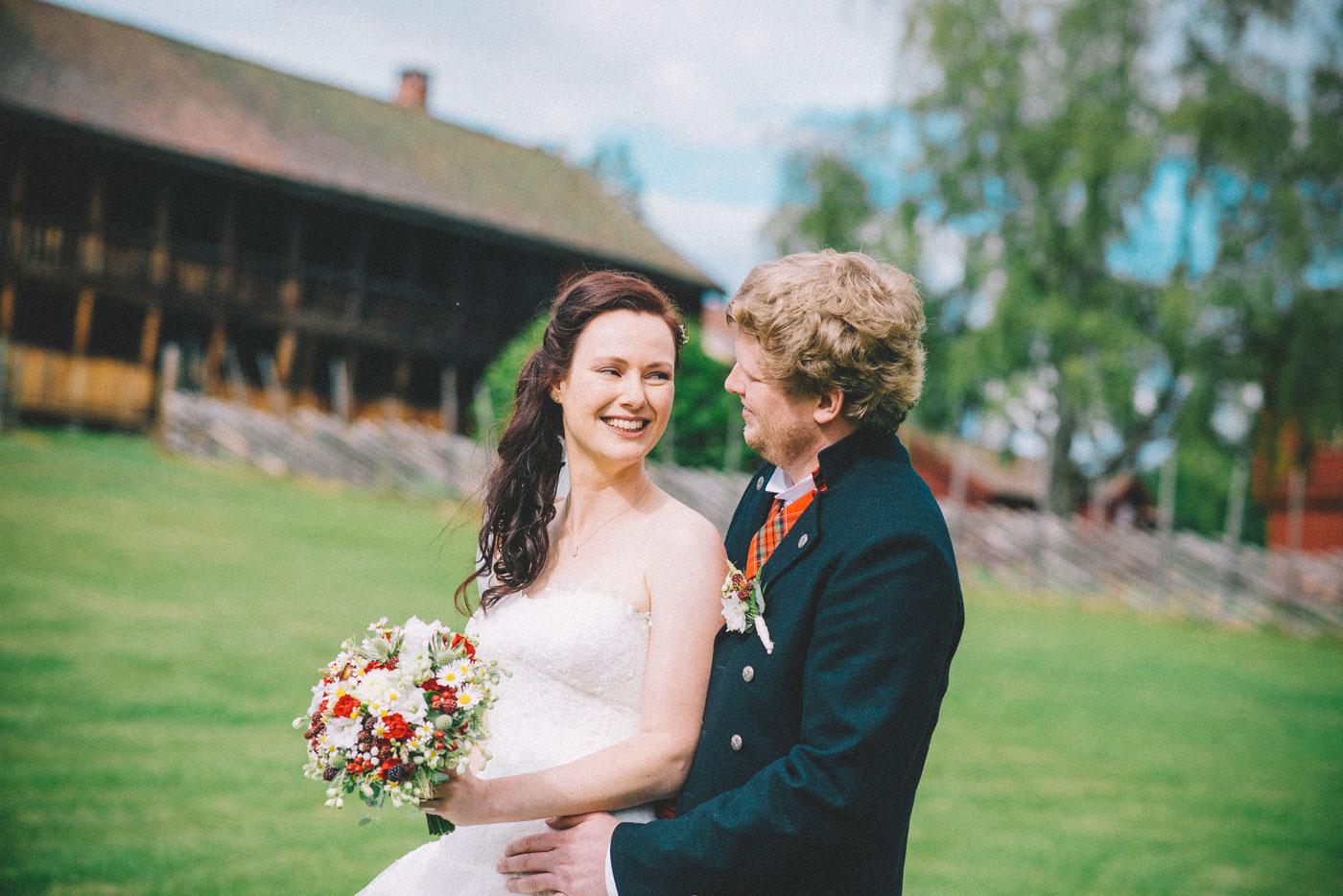 Bryllupsfotografering der brud smiler med blomster, brudgom holder henne